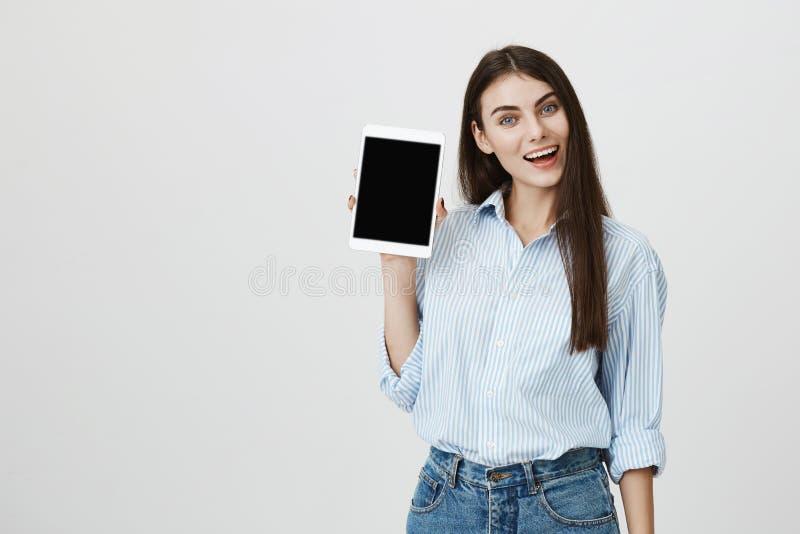 Studioschot van opgewekte en gelukkige vrouw die witte tablet adverteren terwijl het houden van het in opgeheven hand, die zich o stock foto
