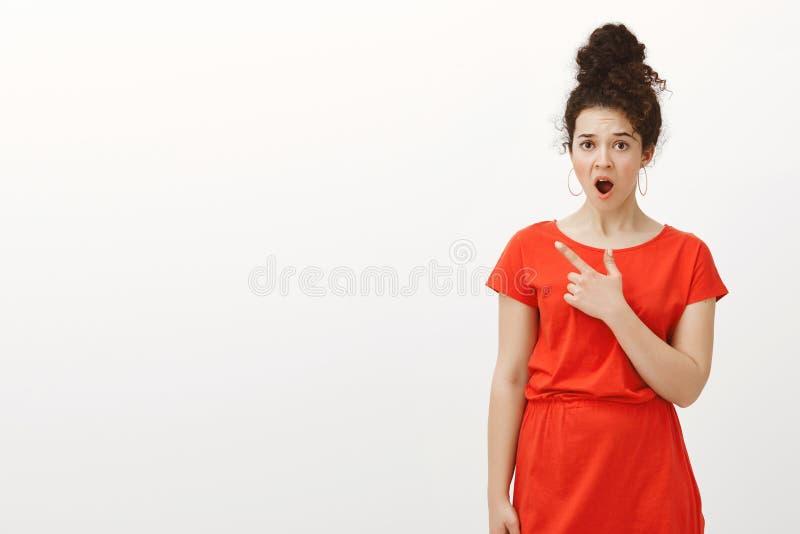 Studioschot van teleurgesteld geschokt meisje met krullend die haar in broodje wordt gekamd, die rode kleding dragen, latend vall stock foto's