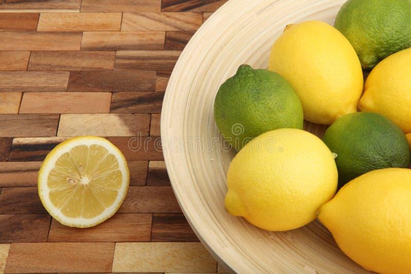Studioschuß einer hölzernen Schüssel füllte mit Zitronen und Kalken lizenzfreie stockbilder