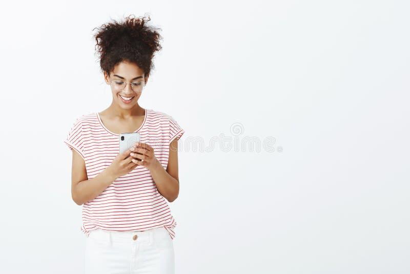 Studioskott av att charma den bekymmerslösa unga kvinnan med brunbränd hud i exponeringsglas och randig t-skjorta som ser och ler arkivbilder