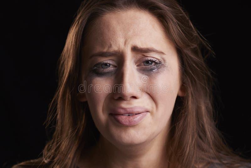 Studioskott av att gråta den unga kvinnan med smetat ögonsmink arkivfoton