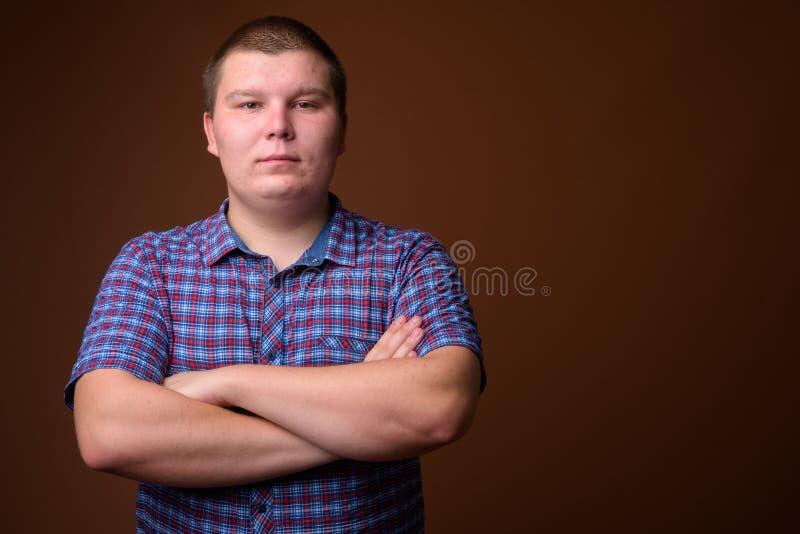 Studioskott av den överviktiga unga mannen mot brun bakgrund royaltyfria foton