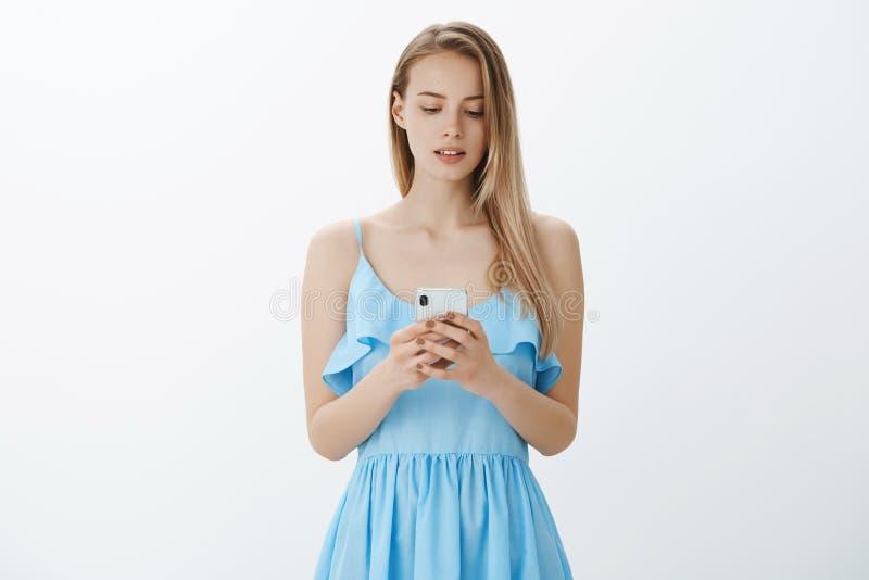 Studioskott av den attraktiva trevliga flickan som uppmuntrar sig att skriva bikt via meddelandeanseende i härlig blå klänning royaltyfri bild