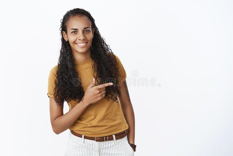 Studioskott av den blyga och gulliga nätta unga afrikansk amerikankvinnan med långt lockigt hår som böjer som att peka rätt med royaltyfria bilder