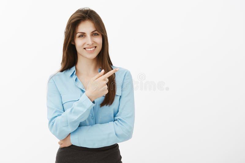 Studioskott av den charmiga utgående europeiska kvinnliga affärskvinnan i blå blus som pekar på det övre högra hörnet med royaltyfria foton