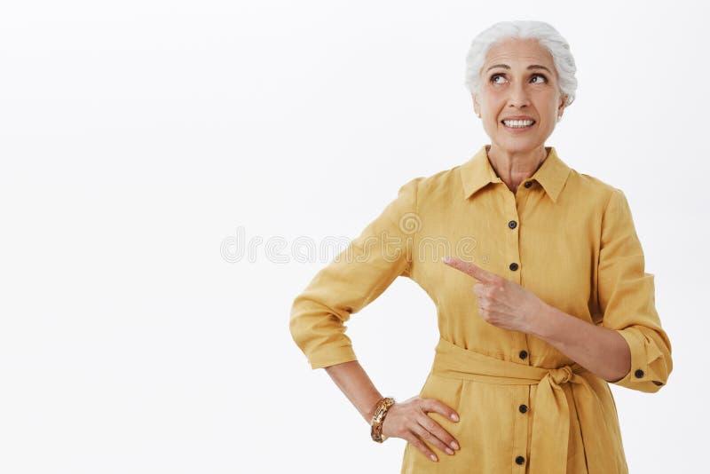 Studioskott av den drömlika och aktiverade gulliga äldre kvinnan för sort i gult stilfullt dikelag som pekar och ser övre royaltyfri fotografi
