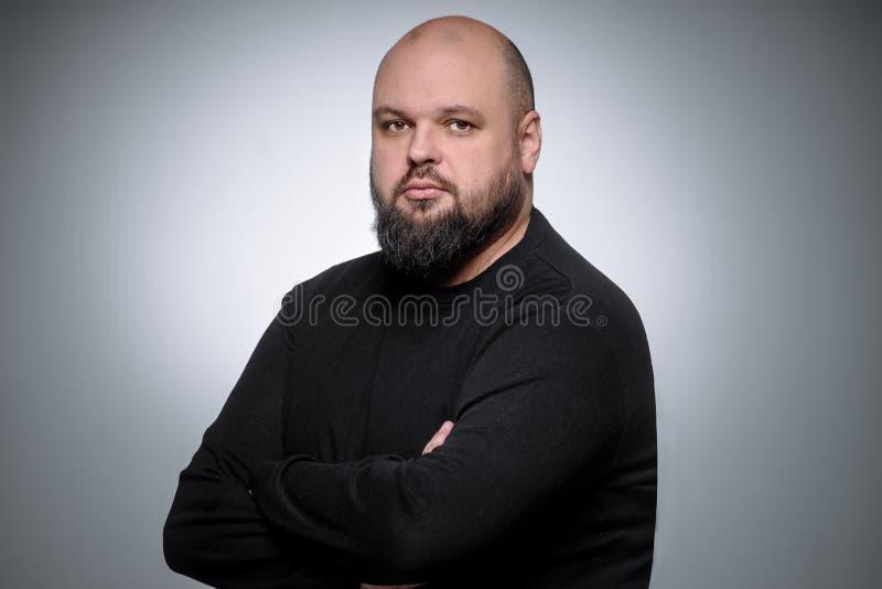Studioskott av den feta affärsmannen som tänker mot grå bakgrund Gullig vuxen man i svart golf Uttrycksfull stående arkivbild