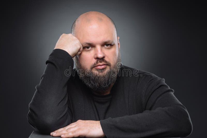 Studioskott av den feta affärsmannen som tänker mot grå bakgrund Gullig vuxen man i svart golf Uttrycksfull stående royaltyfri fotografi