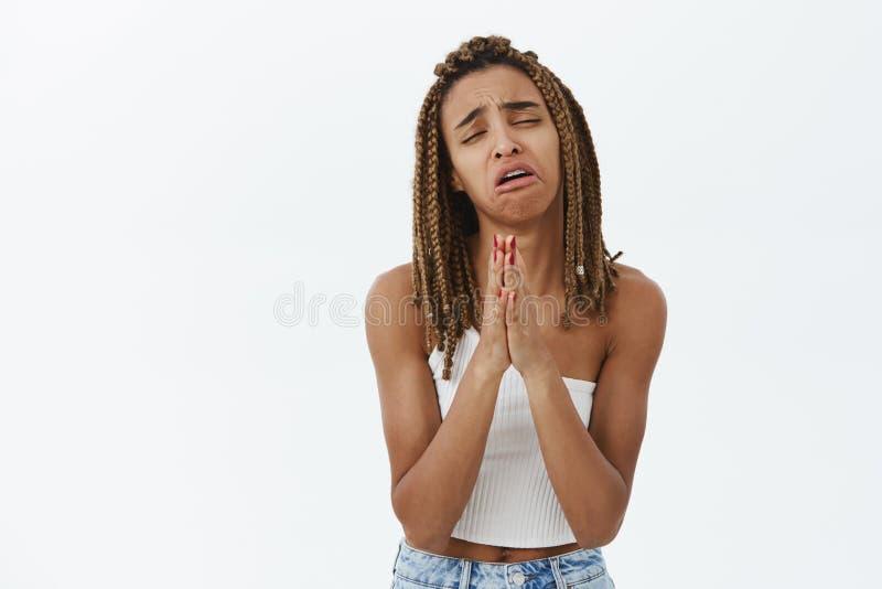 Studioskott av den gn?llande bedr?vliga och desperata gulliga unga m?rkhyade kvinnlign med dreadlocks som g?r ledset luta sig ner royaltyfria bilder