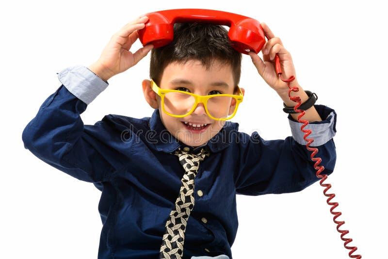 Studioskott av den gulliga lyckliga pojken som ler och sätter den gamla telefonen fotografering för bildbyråer