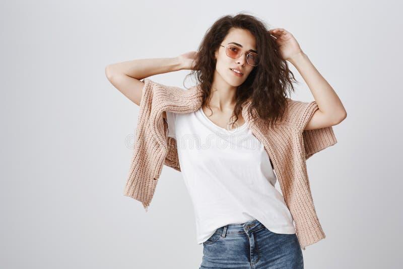 Studioskott av den härliga stads- kvinnan med lockigt hår som sensually lyfter händer och att bära moderiktig solglasögon och trö royaltyfri bild