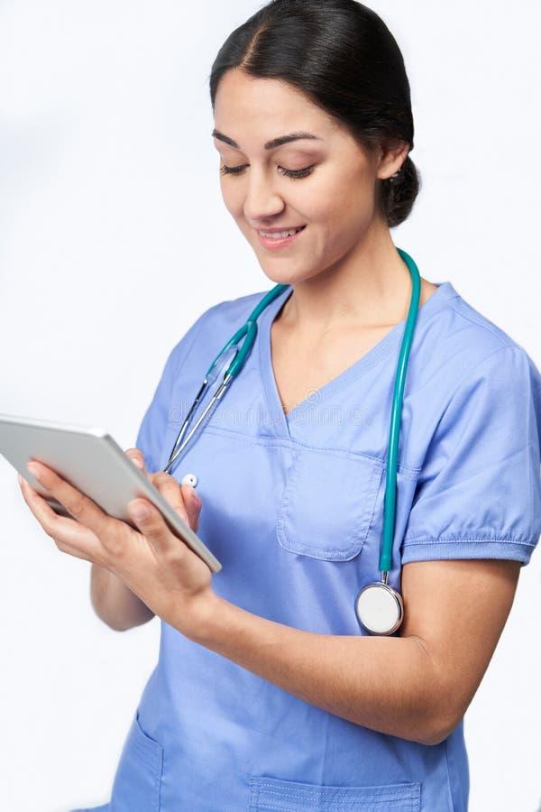 Studioskott av den kvinnliga sjuksköterskaWearing Scrubs Using Digital minnestavlan arkivbild