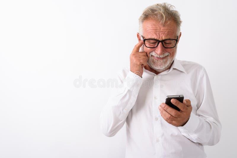 Studioskott av den ledsna höga skäggiga mannen som använder mobiltelefonen medan s royaltyfria foton