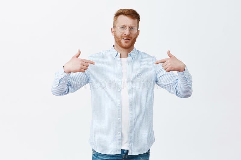 Studioskott av den manliga entreprenören för självsäker stolt rödhårig man i skjorta över t-skjortan som pekar på honom och stirr royaltyfri foto