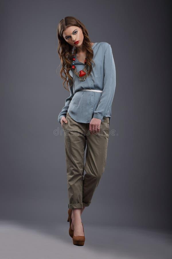 Studioskott av den moderiktiga modemodellen i flåsanden och blus royaltyfri foto