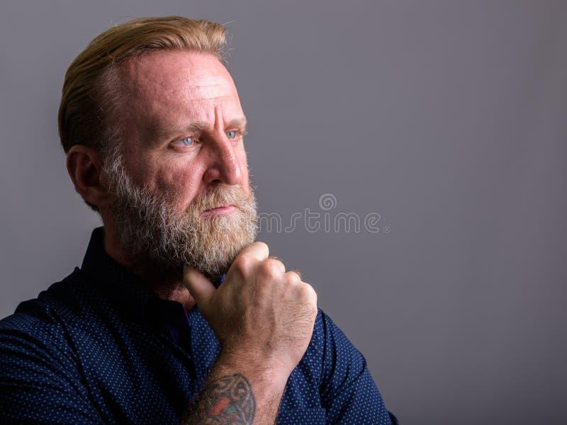 Studioskott av den mogna skäggiga mannen med att tänka för handtatueringar fotografering för bildbyråer