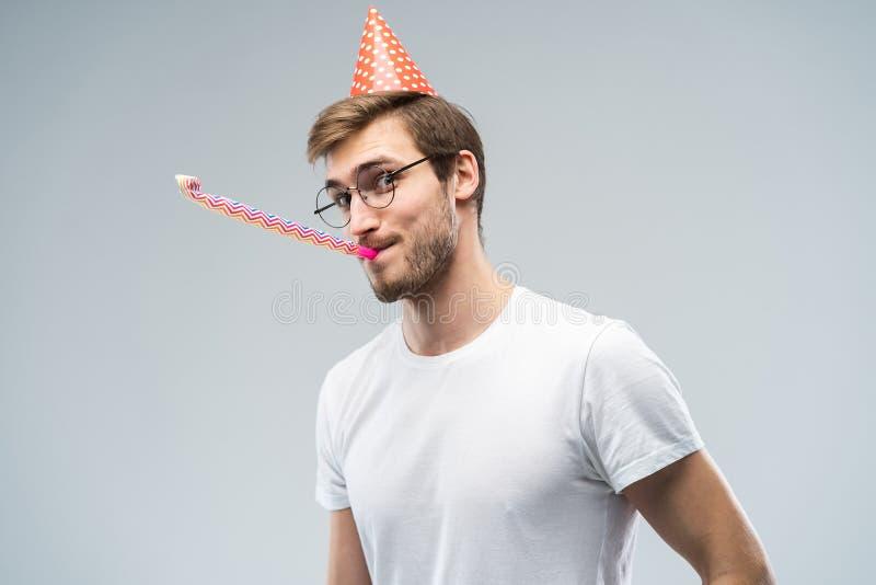 Studioskott av den orakade unga Caucasian mannen som blåser visslingen, medan fira födelsedag och att ha avkopplat och gladlynt fotografering för bildbyråer