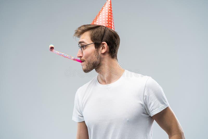 Studioskott av den orakade unga Caucasian mannen som blåser visslingen, medan fira födelsedag och att ha avkopplat och gladlynt arkivfoton