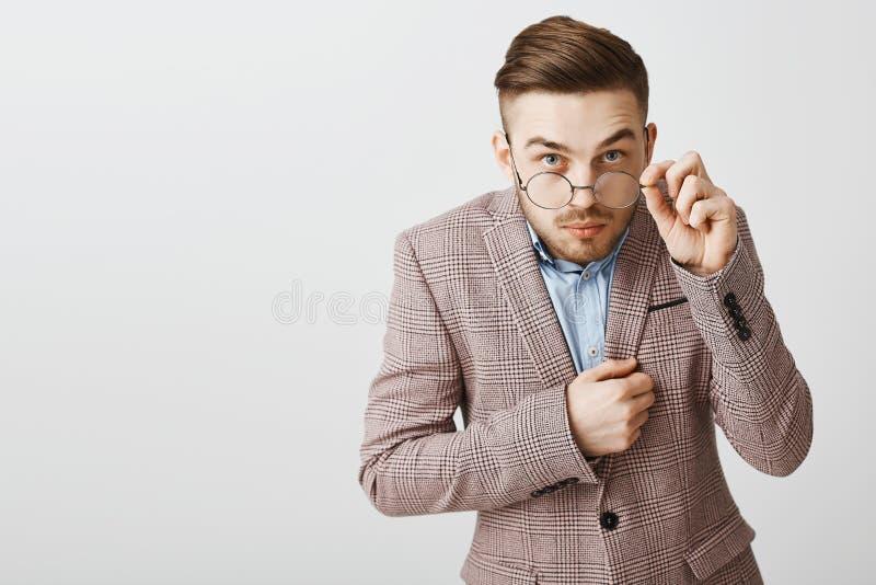 Studioskott av den roliga nerdy manliga kontorsarbetaren i moderiktigt omslag med den moderiktiga frisyren som från under ser att royaltyfri bild