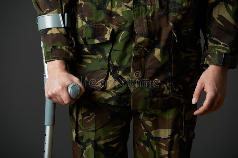 Studioskott av den sårade soldaten Using Crutch royaltyfria foton