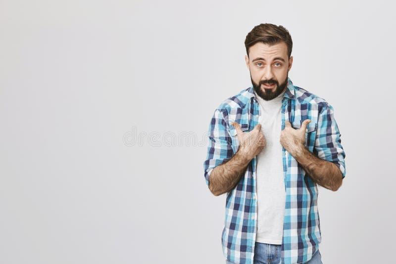 Studioskott av den skäggiga europeiska personen som pekar på honom med kränkt uttryck som står mot grå bakgrund arkivfoton