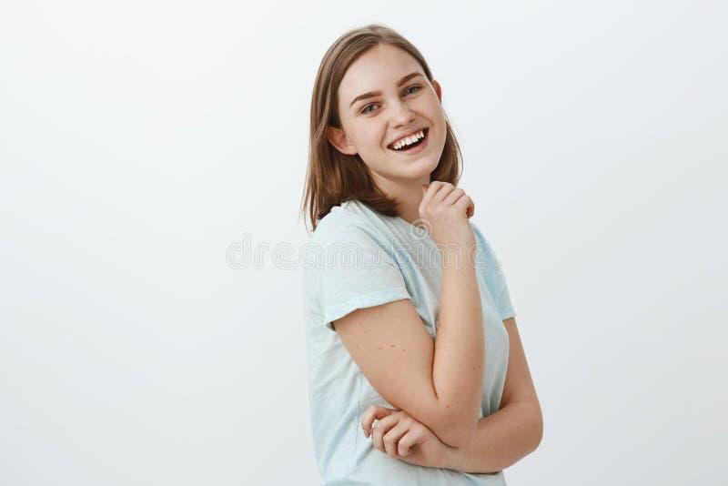 Studioskott av den skickliga idérika och ambitiösa europeiska kvinnan i moderiktigt t-skjorta anseende i profil över den vita väg royaltyfri bild