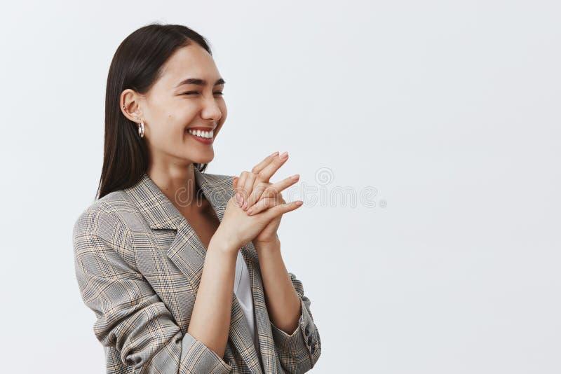 Studioskott av den snygga glade kvinnan som skrattar från glädje och entusiasm som står halva-vänt över grå bakgrund royaltyfria bilder