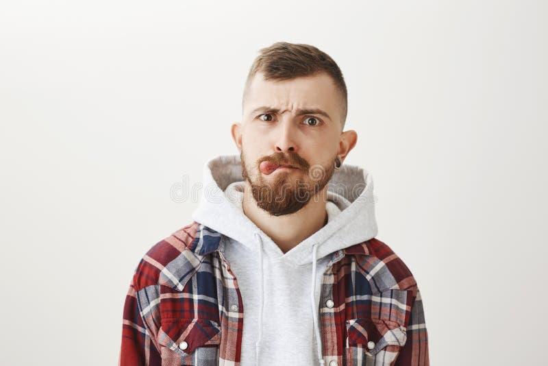 Studioskott av den snygga trängde igenom stads- manliga skateboradåkaren med stilfull frisyr och skäggvisningtungan, rynka pannan arkivbild