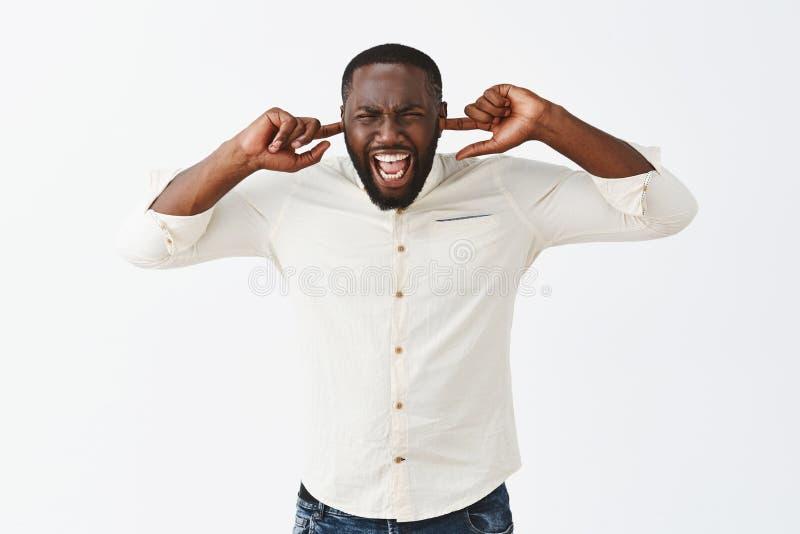 Studioskott av den störda förbannade afrikansk amerikanmannen med skägget i den moderiktiga skjortan, ropa som rymmer pekfingrar  arkivbild