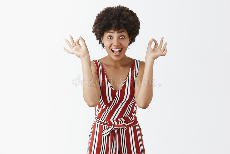 Studioskott av den tillfredsställda och spännande attraktiva mörkhyade kvinnlign i röda randiga overaller som visar ok eller ok g arkivfoton