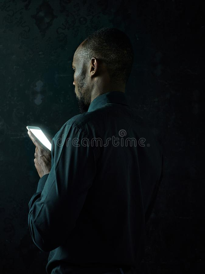 Studioskott av den unga allvarliga svarta afrikanska mannen som tänker, medan tala på mobiltelefonen mot svart bakgrund royaltyfria bilder