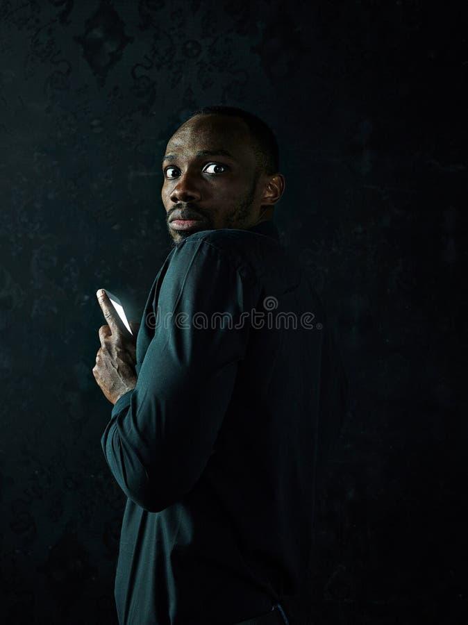 Studioskott av den unga allvarliga svarta afrikanska mannen som tänker, medan tala på mobiltelefonen mot svart bakgrund royaltyfria foton