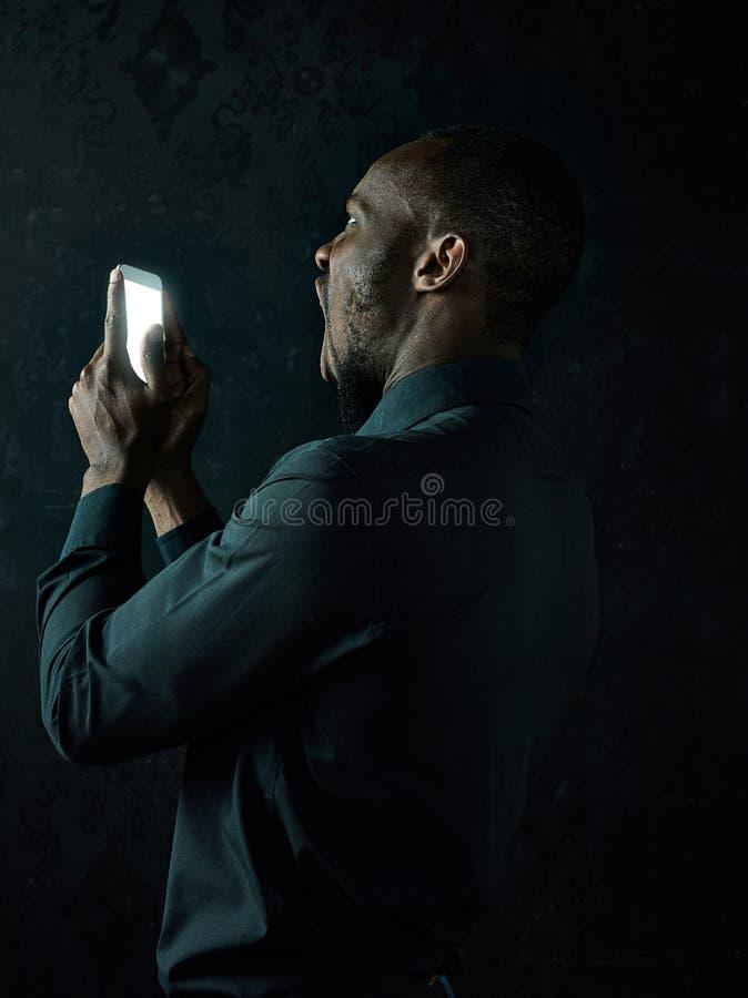 Studioskott av den unga allvarliga svarta afrikanska mannen som tänker, medan tala på mobiltelefonen mot svart bakgrund arkivfoto