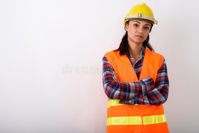 Studioskott av den unga asiatiska kvinnabyggnadsarbetaren med armar c royaltyfria foton