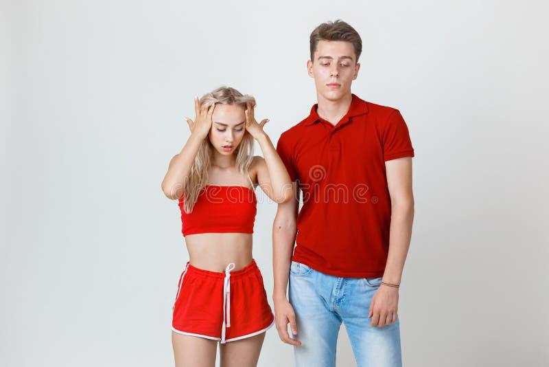 Studioskott av den unga frustrerade kvinnan och mannen Disharmoni i förhållandet Divergens av punkter av sikten royaltyfri foto