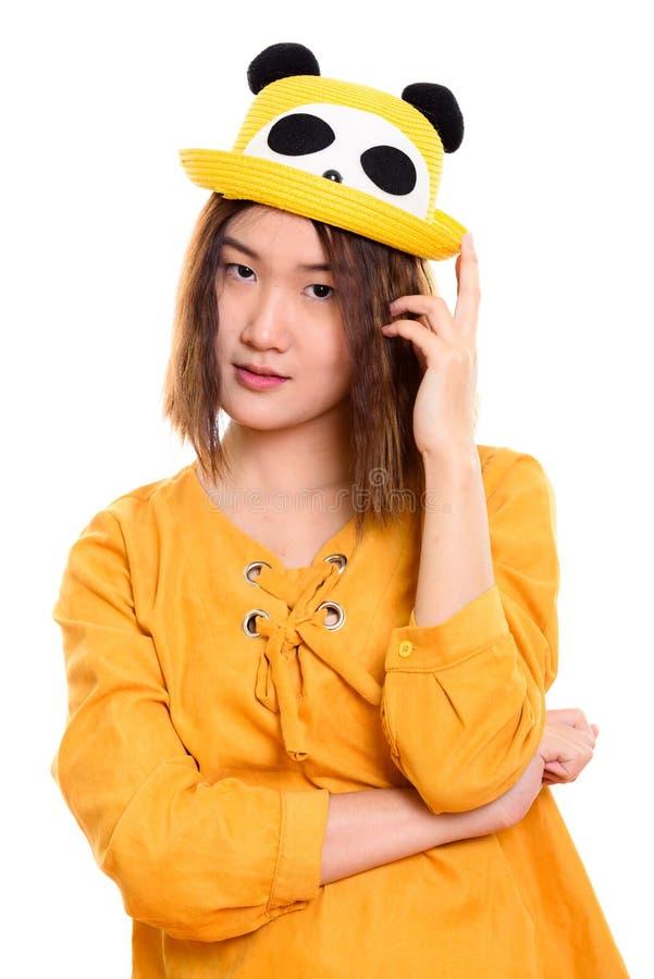 Studioskott av den unga härliga asiatiska kvinnan, medan rymma hatten fotografering för bildbyråer