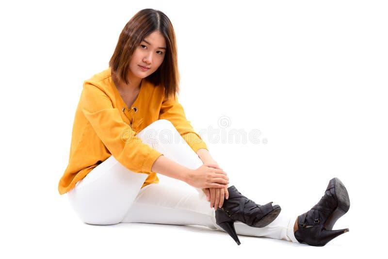 Studioskott av den unga härliga asiatiska kvinnan som sitter på golvet arkivbild