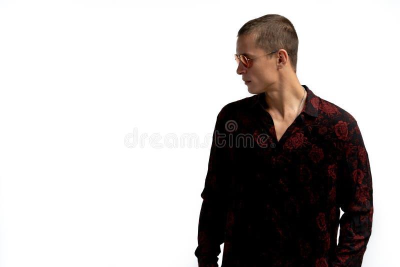 Studioskott av den unga h?rliga allvarliga mannen med kort frisyr, b?rande stilfull svart skjorta med det rosa trycket, att se royaltyfri fotografi