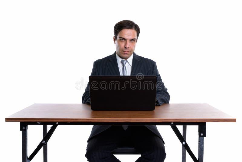 Studioskott av den unga persiska aff?rsmannen som sitter med b?rbara datorn p? arkivbilder