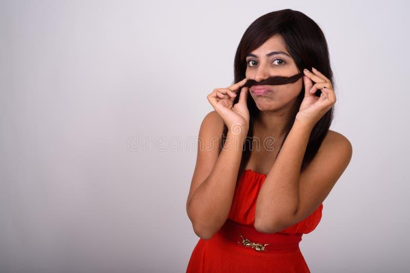 Studioskott av den unga persiska kvinnan som använder hår som mustaschstund fotografering för bildbyråer