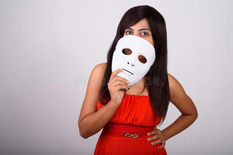 Studioskott av den unga persiska kvinnan som täcker framsidan med den vita maskeringen arkivbilder