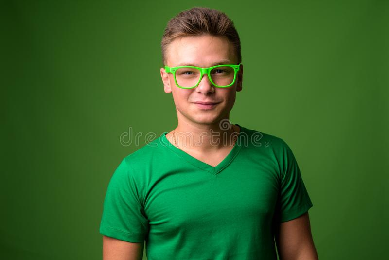 Studioskott av den unga stiliga mannen mot grön bakgrund arkivfoton