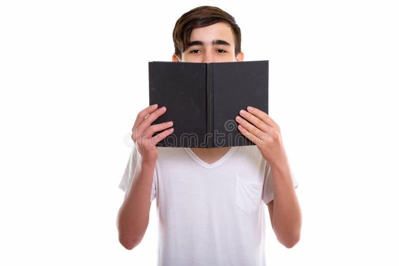 Studioskott av den unga stiliga persiska tonårs- pojken som bakom döljer fotografering för bildbyråer