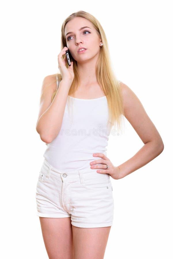Studioskott av den unga uttråkade tonårs- flickan som talar på mobiltelefonen arkivbild