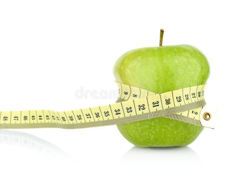 Studioskott av det hela gröna sunda äpplet med måttband royaltyfri bild
