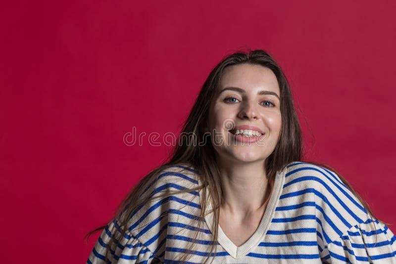 Studioskott av en älskvärd härlig kvinna mot en tom röd studiovägg royaltyfria foton