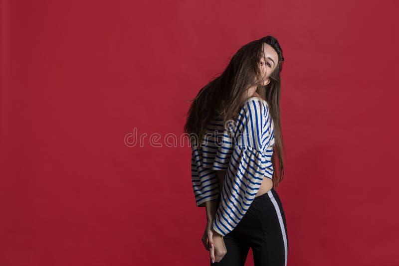 Studioskott av en älskvärd härlig kvinna som isoleras mot en tom röd studiovägg royaltyfria foton