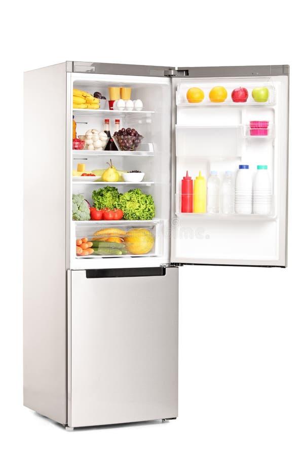 Studioskott av en öppen kyl mycket av sunda livsmedelsprodukter arkivbilder