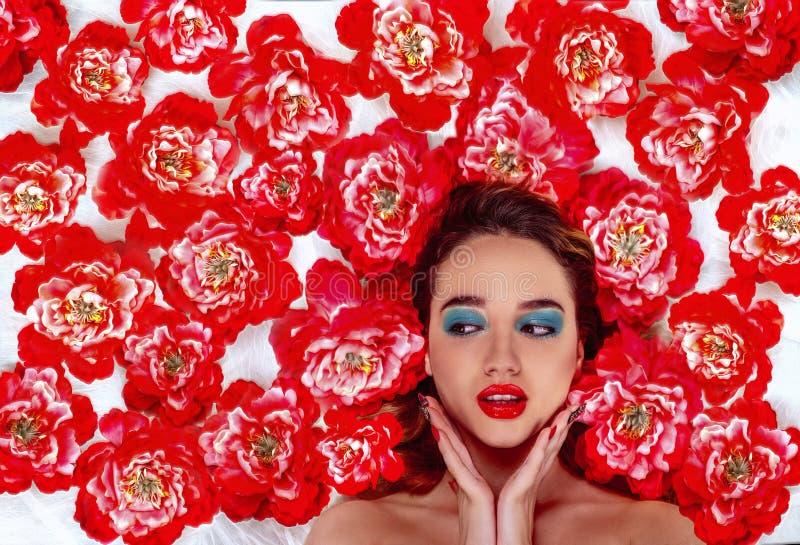 Studioskott av en härlig flicka med makeup som omges av röda vallmo royaltyfri bild