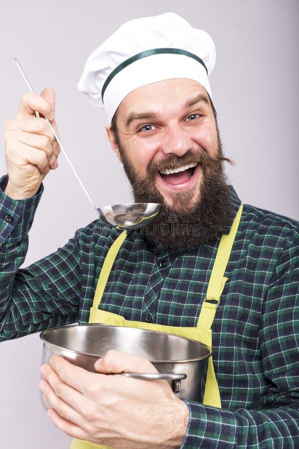 Studioskott av en kock med skäggavsmakningsoppa med royaltyfri bild